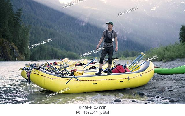 Man looking away while standing on raft at riverbank against mountain