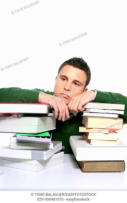 Young unhappy student with much homework and stacked books over white