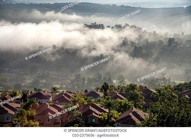 Early morning sun dissipates sea mist around residential homes in Crown Valley in coastal Laguna Niguel, CA