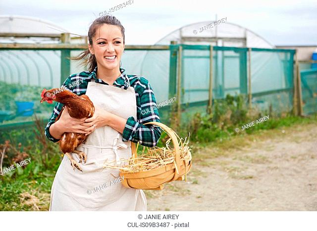 Woman on chicken farm holding chicken