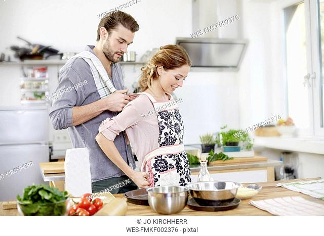 Man helping woman putting on apron in kitchen