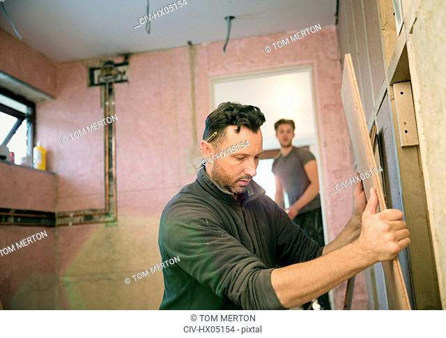Construction worker holding wood board, framing house