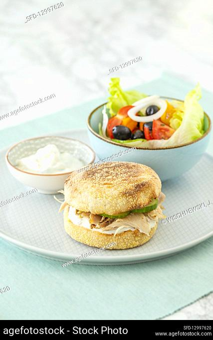 A toast burger with chicken and a colourful salad