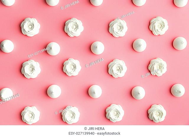 Sweet white meringue on pink background. Top view