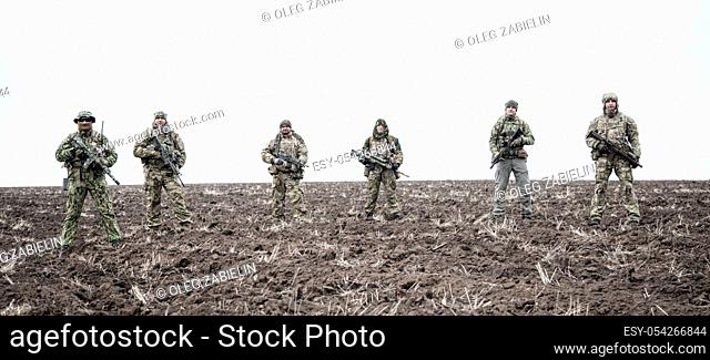 Army soldiers on march. Elite forces fighters group, commando tactical unit, reconnaissance team members in camouflage uniform, walking in line