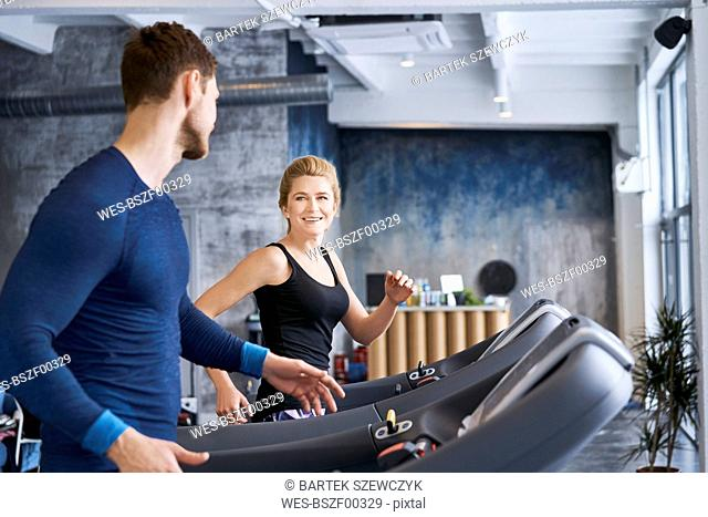 Man and woman talking during treadmill exercise at gym