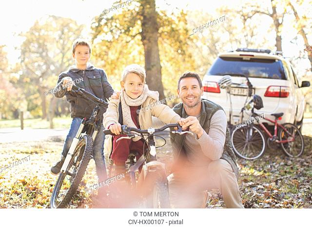 Portrait father and sons with bicycles in autumn park