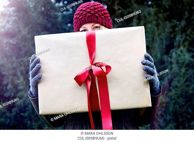 Woman holding up Christmas present with red ribbon