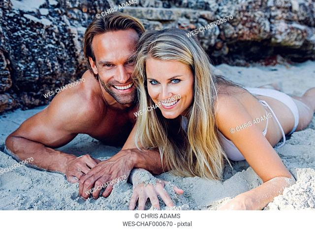 Smiling couple lying on the beach