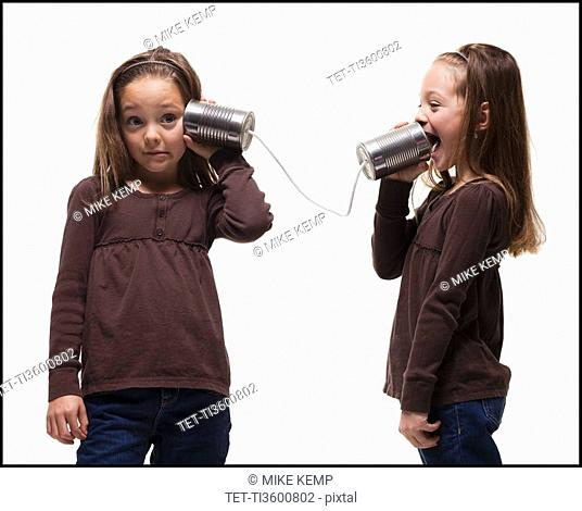 Girls playing with tin can phones