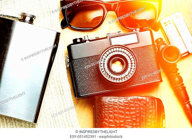 Accessories of the creative person. 35-mm film camera, exposure meter in leather case, steel flask, sunglasses and smoking set on wooden background