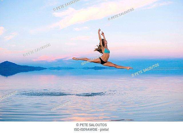 Female ballet dancer jumping mid air over lake, Bonneville Salt Flats, Utah, USA