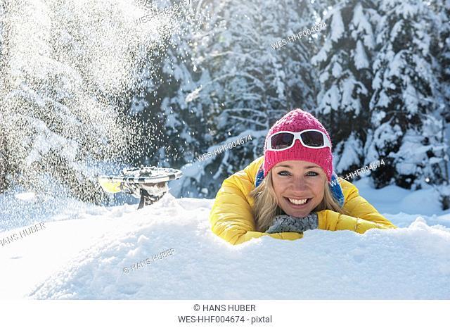 Austria, Salzburg State, Altenmarkt-Zauchensee, Smiling young woman lying in snow, portrait