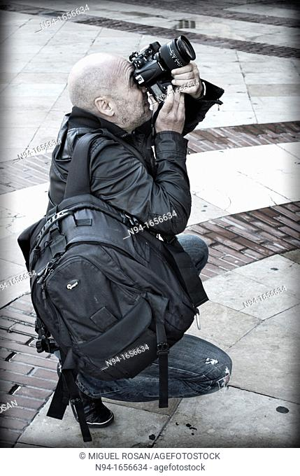 Professional Photographer backpacking, crouching and concentrate, taking photos with a digital SLR camera