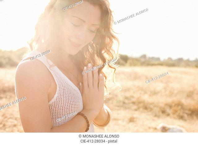 Serene boho woman with hands at heart center in sunny rural field