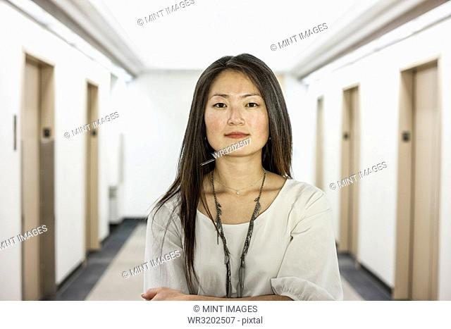 An Asian businesswoman standing alone in her office space