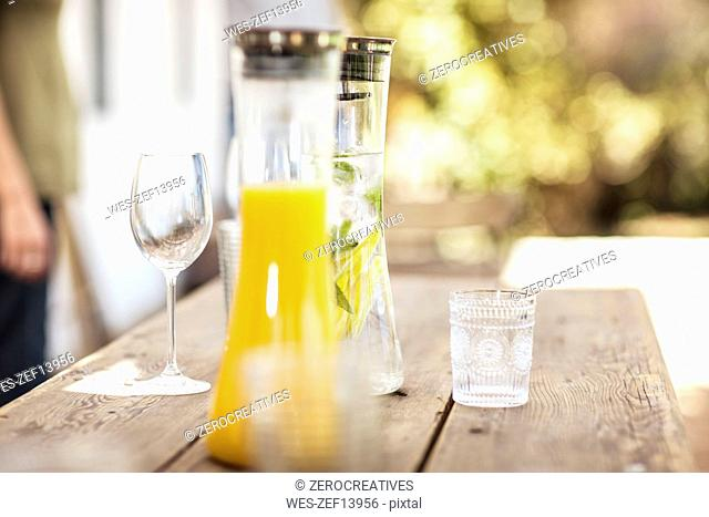 Carafe with refreshing drink outdoors on table