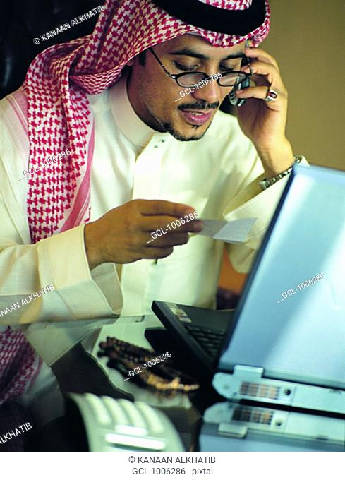 Saudi businessman using mobile phone and laptop in his office