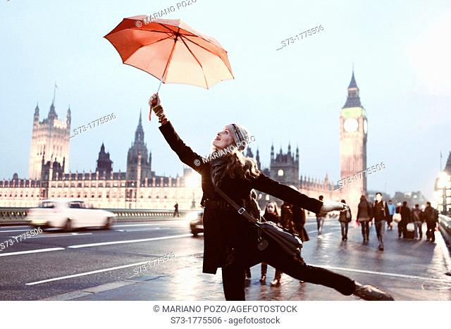 Woman with umbrella and view of the Houses of Parliament and Westminster Bridge, London, England