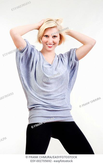 blond girl in oversized gray shirt looking smiling - isolated on white