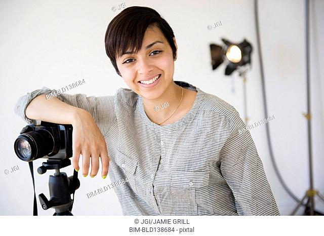 Mixed race photographer smiling in studio