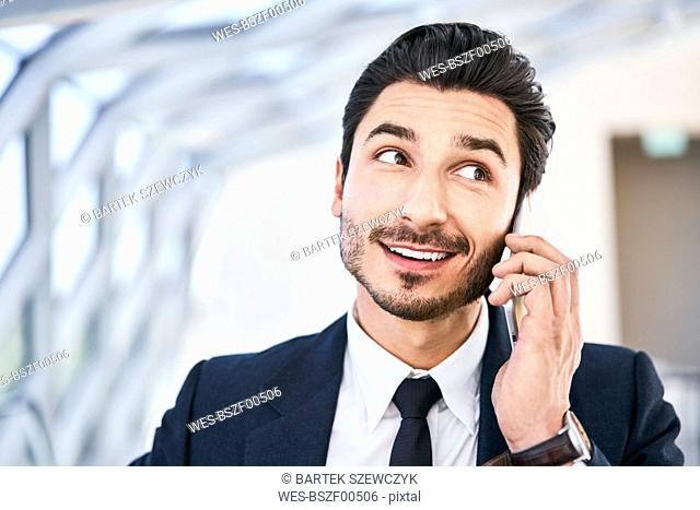 Portait of smiling businessman on cell phone