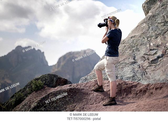 Woman photographing in mountains