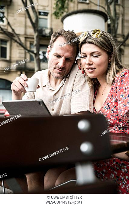 Couple looking at tablet at an outdoor cafe