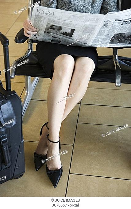 Businesswoman waiting in airport departure lounge, reading newspaper, low section, front view