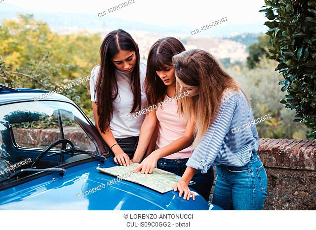 Friends reading route map on car bonnet in countryside