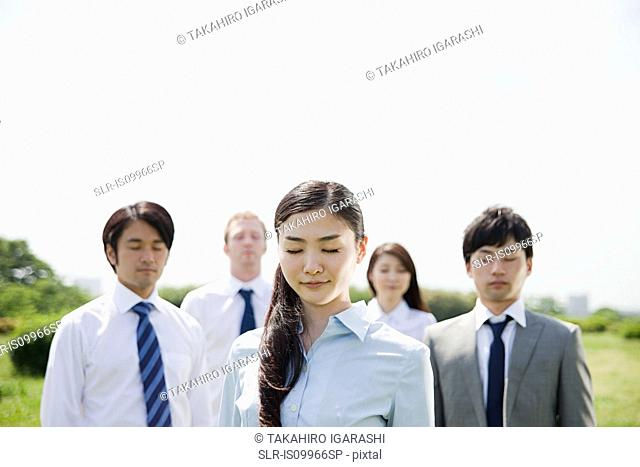 Businesspeople with eyes closed