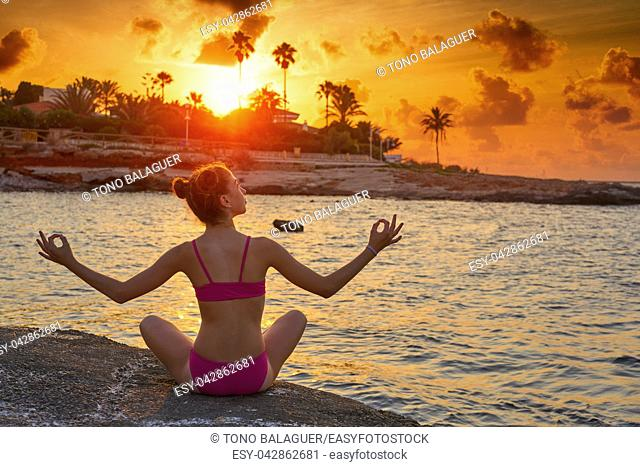 Girl silhouette at beach sunset open arms yoga mudras fingers relaxed sitting