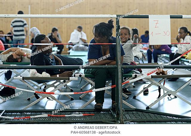 A family from Eritrea sits on cots set up in a gymnasium on the grounds of the German Federal Police in Rosenheim, Germany, 04 August 2015