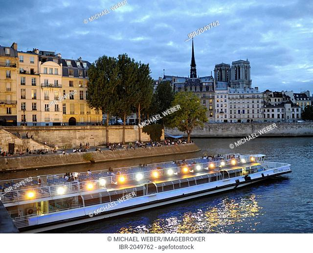 Bateaux Mouches on the Seine, excursion boat with spotlights, Notre Dame de Paris or Notre Dame Cathedral at back, Ile de la Cité, Paris, France, Europe