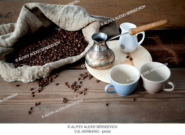Coffee beans and coffee pot on wooden table