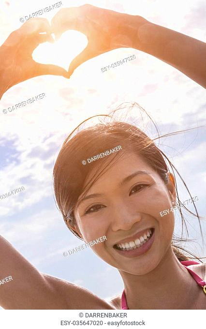 Beautiful young smiling Chinese Asian woman girl on a beach in a bikini, making a hand heart shaped finger frame