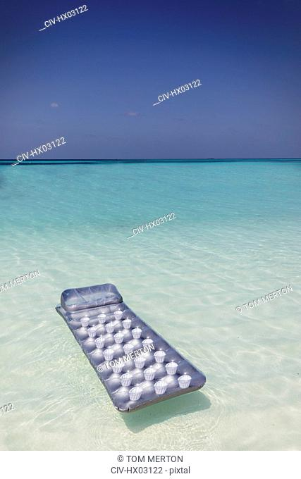 Inflatable raft floating on tranquil blue tropical ocean
