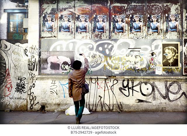 Man taking picture of a graffiti on wall. East London, London, England