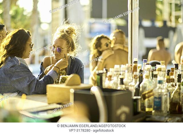 Two women drinking cocktails at bar, Hersonissos, Crete, Greece