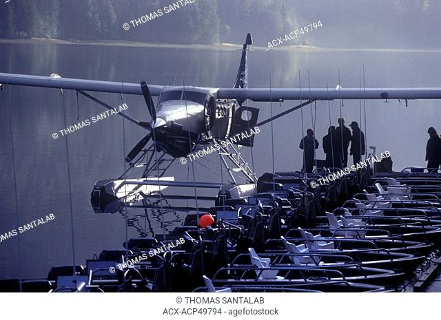 Float plane waits at the dock in the early morning mist at a Queen Charlotte Islands floating fishing lodge in northern British Columbia, Canada