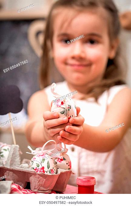 Little cute girl with Easter eggs in hand, the concept of the Easter holidays