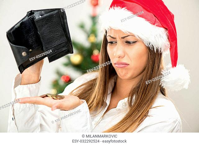 Young beautiful businesswoman wearing santa hat and looks worried at empty wallet