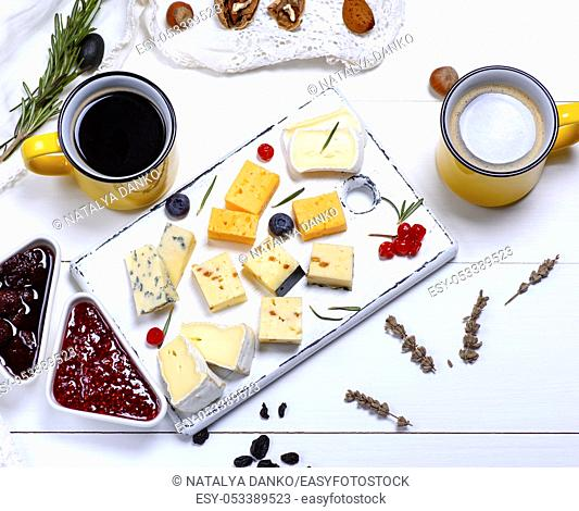 small pieces of brie cheese, roquefort, camembert, cheddar and cheese with walnuts on a white wooden board, next to two yellow ceramic mugs with black coffee