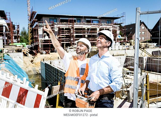 Smiling construction worker talking to man on construction site