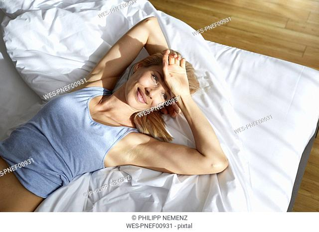 Portrait of smiling blond woman lying in bed in the morning