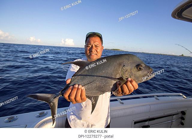 Fisherman holding fresh caught Jack fish (Carangidae); Tahiti
