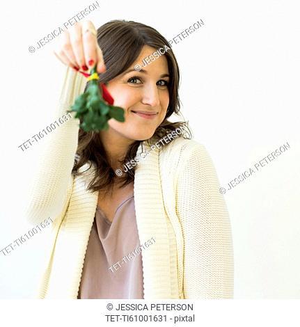 Studio shot of woman holding Christmas wreath