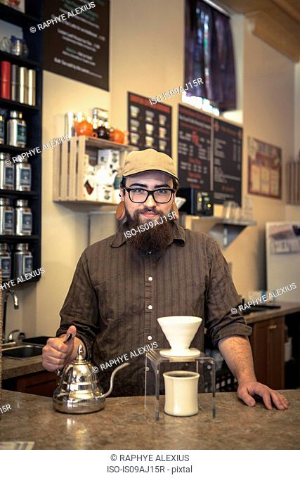 Portrait of barista serving coffee on cafe counter