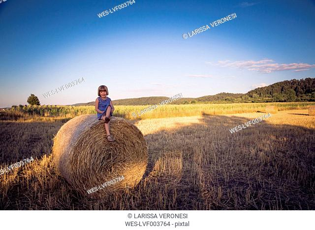 Little girl sitting on straw bale