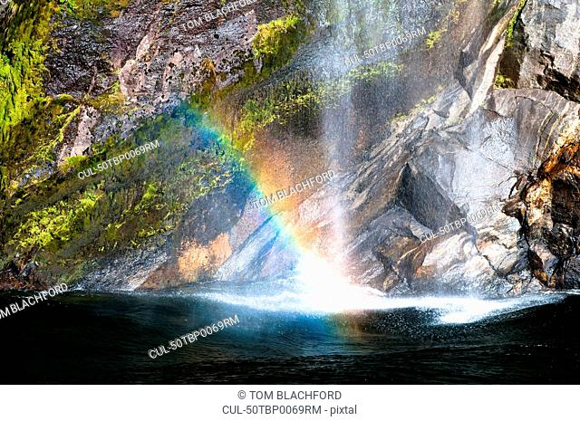 Rainbow in waterfall over cliffs